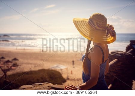 Woman looking at the sea sitting close to the beach with a low sun