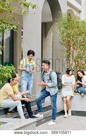 Vietnamese College Students Talking And Resting In Backyard Of Campus During Break