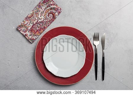 Simple Minimal Table Setting With Two Dishes, Silverware And Napkin On Gray Concrete Background. Con