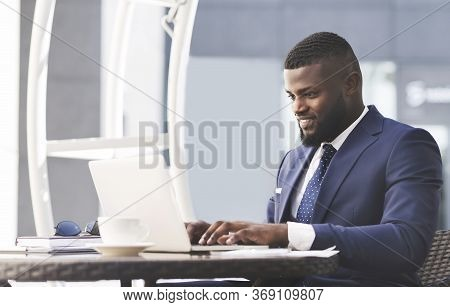 Successful Black Businessman Working On Laptop Computer Distantly Online Sitting In Outdoor Cafe In