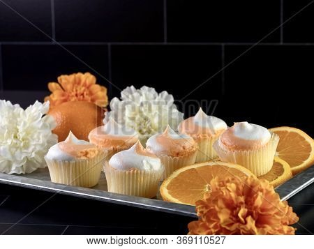 Rustic Metal Tray Filled With Mini Orange Creamsicle Cupcakes Decorated With White And Orange Frosti