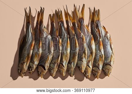 Lots Of Dried Or Jerky Salty Roach, Palatable Clipfish On Pink Background. Famous Beer Snack. Tradit