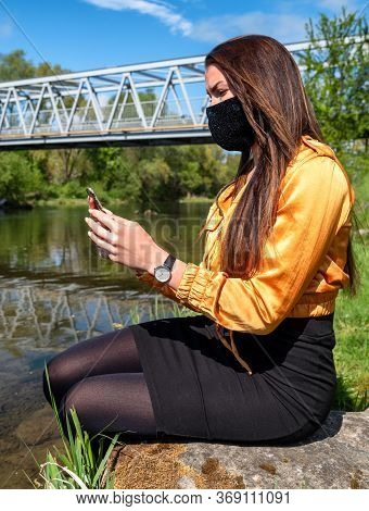 Girl With Face Mask Sitting On The Shore Of The Lake And Looking Into The Cell Phone.
