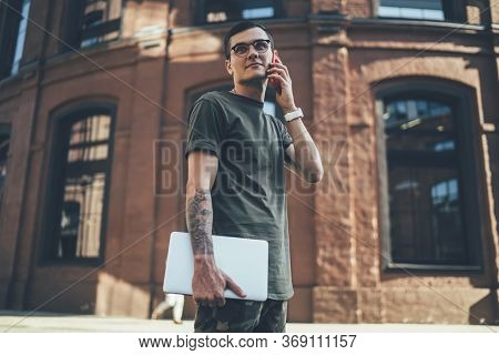Carefree Young Male Student Using Smartphone In Street