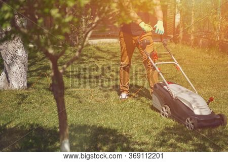 Professional Gardener In Casual Outfit And Gloves Is Trimming Green Grass With Modern Lawn Mower On