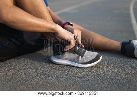 Running Shoes. Closeup Of Man Tying Shoe Laces. Sport Fitness Runner Getting Ready For Jogging In Th
