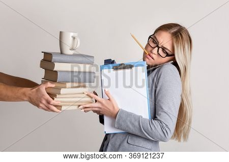 Pressure At Work. Indifferent Boss Overloading Woman With Work. Gives Her A Lot Books And Cup For Co