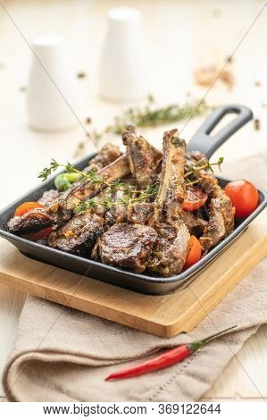 Fried Lamb Chops With Fried Onions, Garlic And Fresh Herbs. A Large Portion Is Served On A Plate And