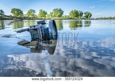 small waterproof action camera in a rugged cage partially submerged with a mini tripod in a calm lake, morning spring scenery in Colorado