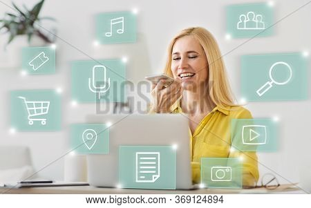 Woman Using Voice Search On Smart Phone Doing Shopping And Browsing Internet Sitting At Laptop In Of