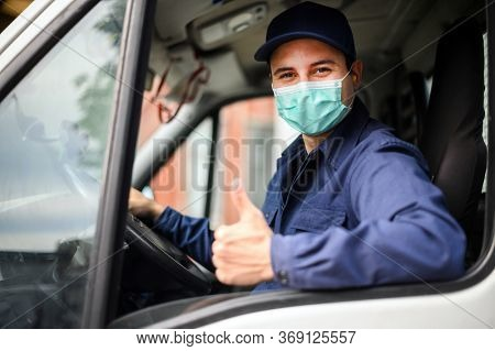 Portrait of a van driver giving thumbs up and wearing a mask, coronavirus concept