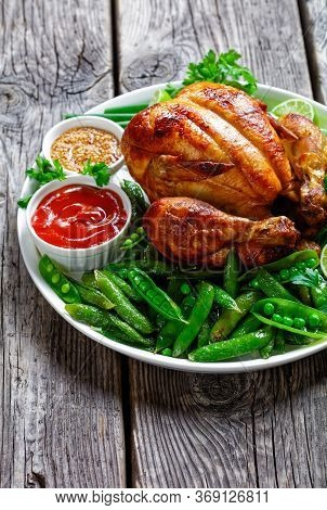Whole Roast Chicken Served With Fried Pods Of Green Peas, Fresh Green Onion, Parsley, Lime, Tomato S
