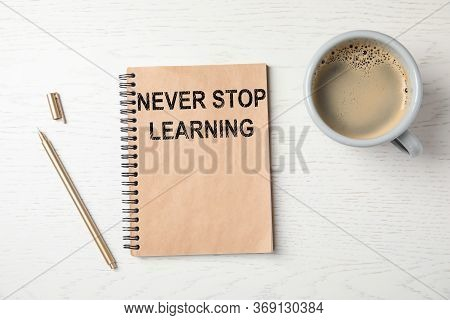 Notebook With Phrase Never Stop Learning, Pen And Cup Of Coffee On White Wooden Background, Flat Lay