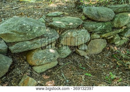 Closeup View Of The Dry Stacked Stone And Rock Wall Covered With Lichens And Moss That Is A Rustic R