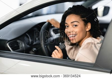 New Car Concept. Joyful Black Lady Buyer Showing Auto Key Sitting In Drivers Seat In Automobile In D