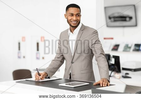 Selling Cars. Auto Dealer Man Standing At Counter Working In Automobile Dealership Office.