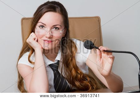 Business Theme:  Portrait Of Successful  Businesswoman With Speakerphone In An Office Environment.