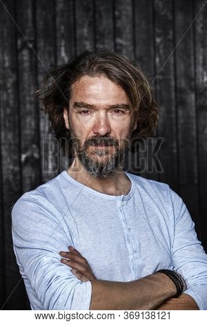 Bearded Man Has A Serious Face Expression On His Face. Arms Crossed. Portrait Of A Handsome Mature M