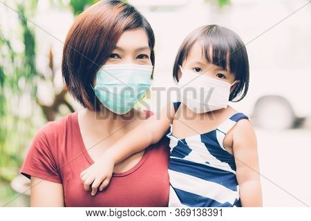 Mother Take Care Daughter With Face Mask For Protection Disease Flu Or Covid-19 Outdoors, Mom Wearin