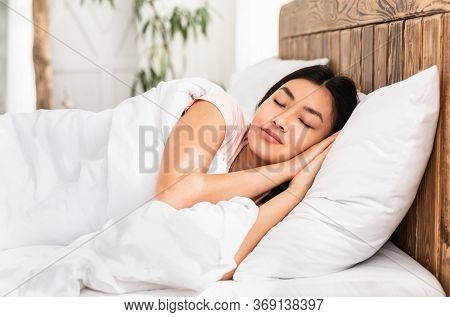 Peaceful Asian Girl Sleeping Resting Lying In Comfortable Bed In Bedroom At Home. Healthy Sleep Conc