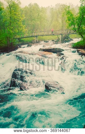 Travel And Hiking. Tourist Woman Standing On Bridge, Enjoying Waterfall Torrential River Along The A