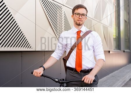 Contemporary man in eyeglasses and formalwear looking at you while moving forwards along wall of contemporary building