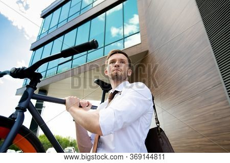 Contemporary office worker in formalwear carrying bicycle while leaving work and moving towards road to go have some rest