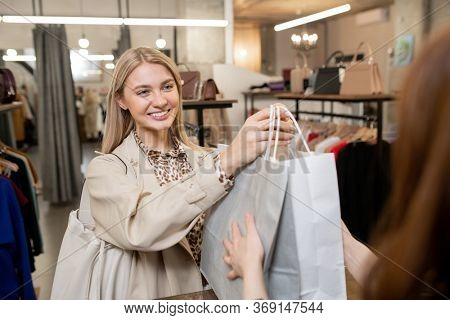Happy young smiling woman passing paperbags with new clothes to shop assistant while holding them over payment counter in boutique