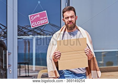 Unemployed Guy With Empty Signboad Near Closed Door Office Or Cafe. Unemployment During Coronavirus