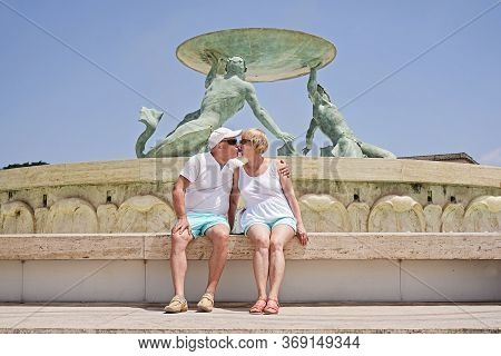 Middle-aged Couple Of Baby Boomers People Posing For Photograph Opposite Famous Fountain In Valletta