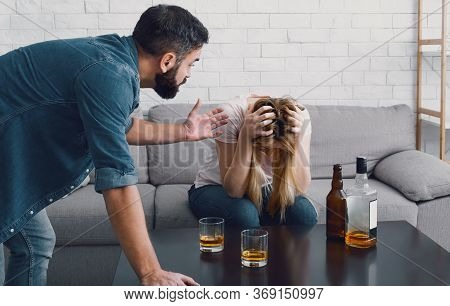 Drunken Scandal. Woman Holds Her Head And Sitting On Sofa, Angry Man Swears With Wife Bottles And Gl