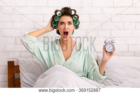 Overslept Girl Holding Alarm Clock Sitting In Bed At Home Being Late For Work In The Morning. Oversl