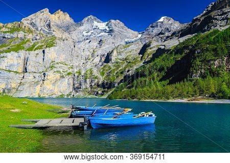 Popular Hiking And Leisure Place With Lake Oeschinensee. Moored Recreation Boats And High Mountains
