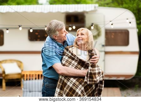 Caring Senior Man Covering His Beloved Woman With Warm Blanket Near Motorhome At Camping Site