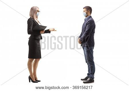 Full length profile shot of a businesswoman wearing a protective face mask and talking to a man also wearing a mask isolated on white background
