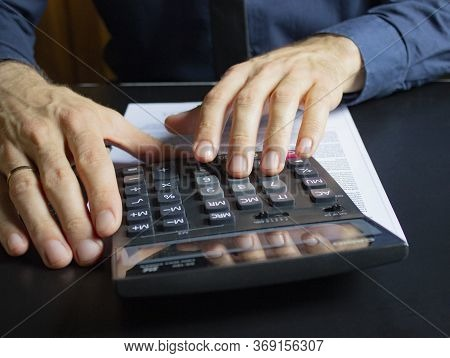 A Young Businessman Calculates On The Calculator The Difference Between The Deficit And The Surplus