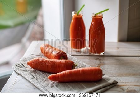 Freshly Squeezed Carrot Juice On Light Wooden Background. Source Of Vitamin A, Carotene, And Retinol