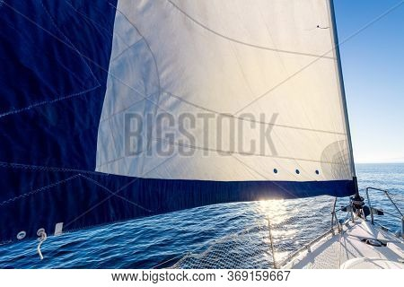 Sailing on a yacht at calm weather with sun. A view from the yacht's deck to the bow and sails. Sail boat with set up sails gliding in open sea. Greece, Europe