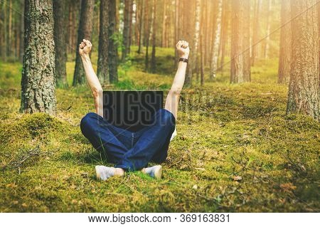 Telecommuting - Man With Laptop Laying In The Moss In The Forest With Hands Raised