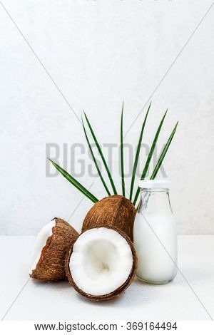 Fresh, Healthy Vegan Plant Base Coconut Milk With Whole Nuts And Pulm Leaf On The White Background.