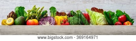 Arrangement Of Fruits And Vegetables In Many Appetizing Colors In A Row On Wooden Light Gray Backgro