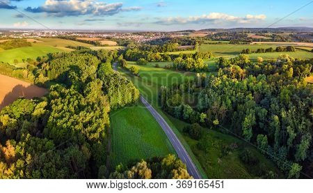 Idyllic German Landscape Shot From Above In Early Morning Sunlight: Meadows And Forests With Blue Sk