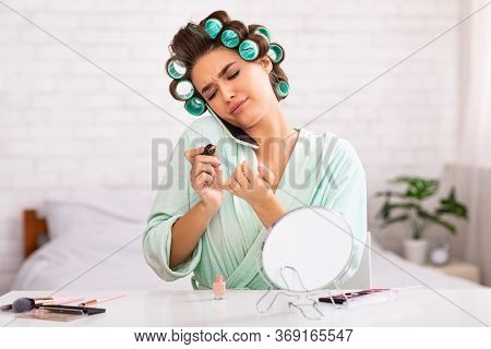 Discontented Housewife Talking On Cellphone Doing Nails Manicure Sitting At Home. Domestic Lifestyle