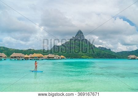 Tahiti beach vacation luxury resort hotel in Bora Bora, French Polynesia. Paddleboarding watersport leisure activity SUP paddle woman, French Polynesia. Mount Otemanu landscape summer holiday.