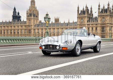 LONDON, UK - CIRCA NOVEMBER 2011: A silver Jaguar E-Type on Westminster Bridge with the Palace of Westminster in the background.