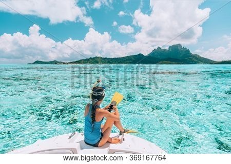 Snorkel diving excursion boat tour from yacht luxury travel influencer going swimming in coral reefs of Tahiti, French Polynesia Bora Bora island.