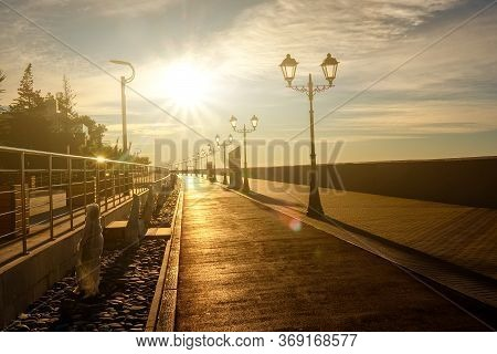 Empty Promenade Overlooking The Sea. The Morning Sun Shines Brightly. There Are No People.