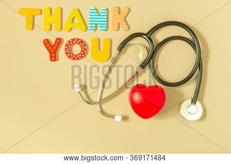 Thank You Words, Medical Stethoscope And Red Heart On Red Background. Flat Lay Of Heart And Stethosc