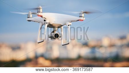 drone with digital camera flying at city street