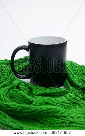 Coffee Cup Nestled In Green Lace Scarf Against A Light Background.  Copy Space On The Black Mug For
